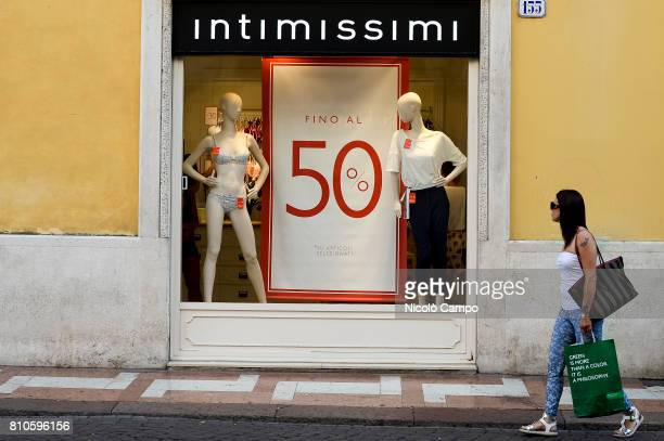 A pedestrian walks in front of a shop window with a writing announcing the sales during the Italian summer sales