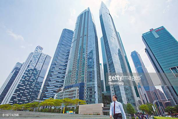 A pedestrian walks in front of commercial buildings in the central business district of Singapore on Friday April 8 2016 Singapore edged past Hong...