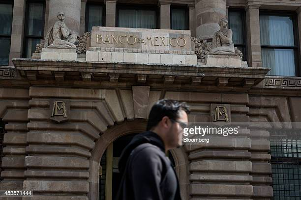 A pedestrian walks in front of the Banco de Mexico headquarters building in Mexico City Mexico on Wednesday Aug 13 2014 Mexican policy makers lowered...