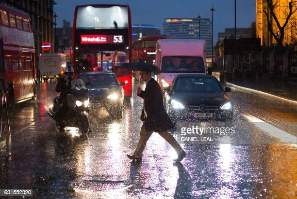 A pedestrian walks in heavy rain near the Houses of Parliament in central London on January 12 2017 Britain's Met Office weather centre issued severe...