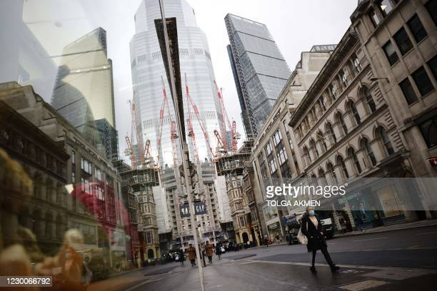 Pedestrian walks in the City of London on December 11, 2020 with the Leadenhall Building in the background - A Brexit trade deal between Britain and...