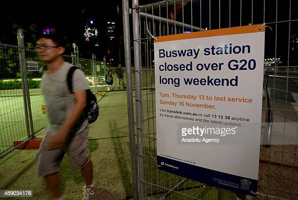 A pedestrian walks near a warning sign hung within security measures at the city center of Brisbane during the G20 summit in Australia on November 15...