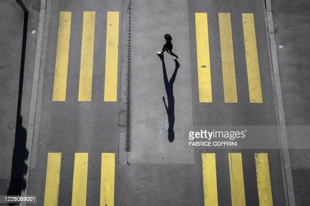 Pedestrian walks on a pedestrian crossing in Lausanne on August 18, 2020.