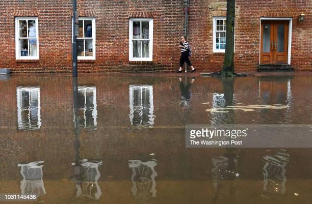 Pedestrian walks on a sidewalk along North Union Street after morning tidal flooding on Monday September 10, 2018 in Alexandria, VA.