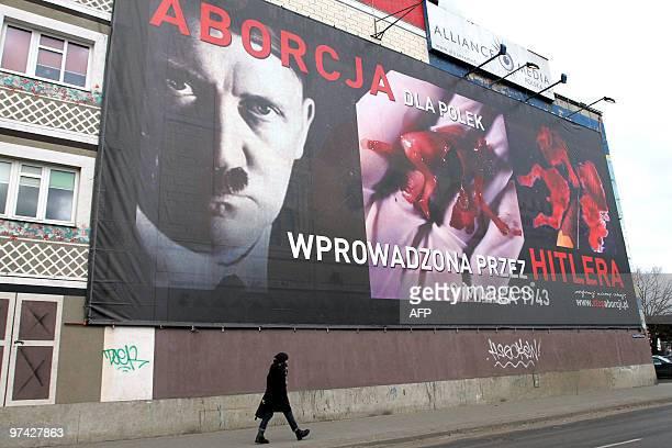 A pedestrian walks on March 3 2010 in Poznan under a billboard showing Adolf Hitler alongside bloodied hackedup fetuses and bearing the slogan...