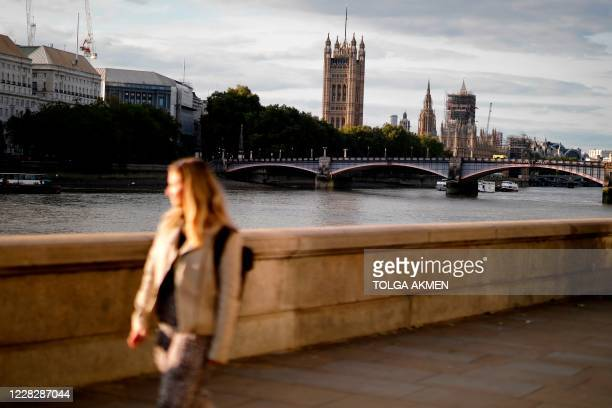 A pedestrian walks on the southbank with the Palace of Westminster behind in London on August 31 on the eve of MPs return to the UK parliament