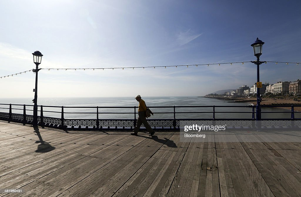 A pedestrian walks on the wooden boards of Eastbourne Pier in Eastbourne, U.K., on Tuesday, April 1, 2014. Pensioners and savers have seen returns on their money shrink since the financial crisis drove interest rates to a record low. Photographer: Chris Ratcliffe/Bloomberg via Getty Images