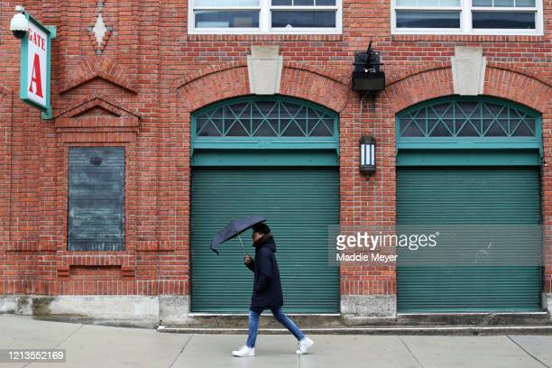A pedestrian walks outside of a closed Fenway Park on March 19 2020 in Boston Massachusetts The NBA NHL NCAA and MLB have all announced cancellations...