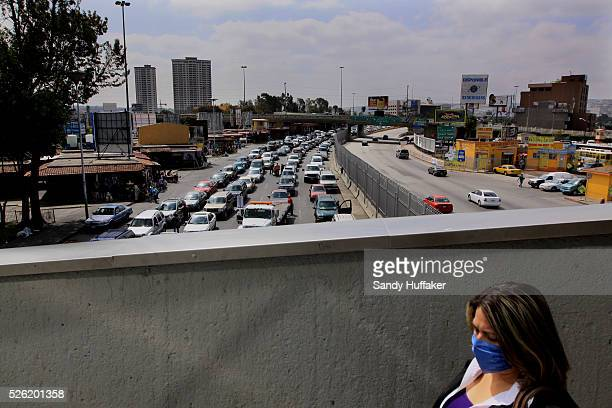 Pedestrian walks over a bridge towards the Mexico-U.S. Border at the Port of Entry in Tijuana, Mexico. The World Health Organization on Wednesday...