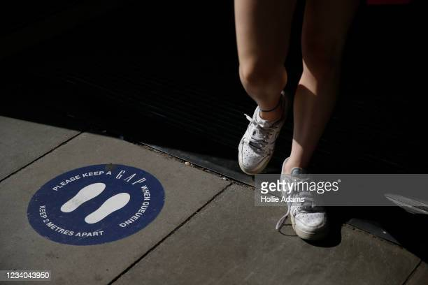 Pedestrian walks over a social distancing notice at Oxford Street on July 18, 2021 in London, England. On Monday, England will drop nearly all...