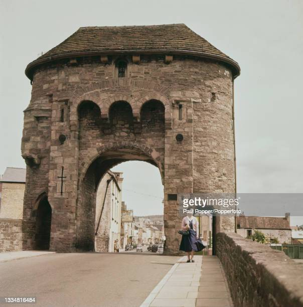 Pedestrian walks over Monnow Bridge, a fortified river bridge with a 13th century gatehouse over the River Monnow in Monmouth, Wales, circa 1960.