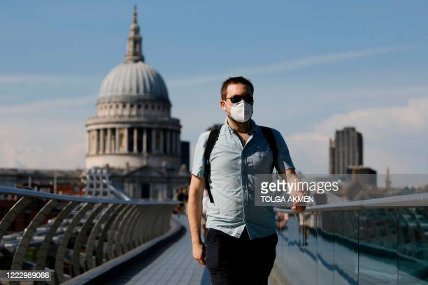 A pedestrian walks over The Millennium Bridge away from St Paul's Cathedral in London on June 26 as temperatures are expected to again be high...