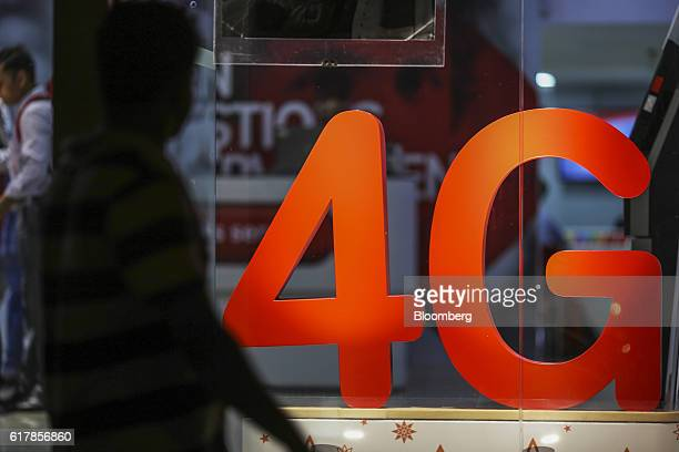 A pedestrian walks past a 4G sign displayed at a Bharti Airtel Ltd store in Mumbai India on Monday Oct 24 2016 Bharti Airtel is scheduled to release...