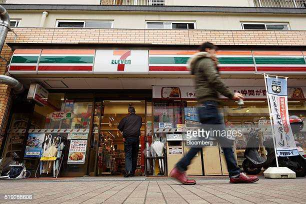 A pedestrian walks past a 7eleven convenience store operated by Seven i Holdings Co in Kawasaki City Kanagawa Prefecture Japan on Tuesday April 5...