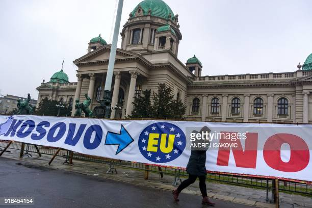 A pedestrian walks past a banner displayed in front of the National Assembly building in Belgrade on February 13 2018 A decade after its southern...