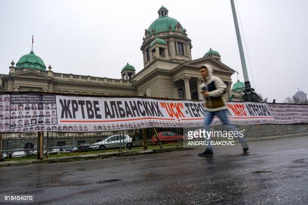 A pedestrian walks past a banner showing portraits of Serbian victims during the war in Kosovo in front of the National Assembly building in Belgrade...