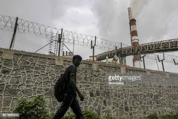 A pedestrian walks past a barbed wire fence as smoke rises from a chimney at the Tata Power Co Trombay Thermal Power Station in Mumbai India on...