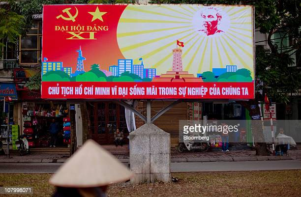 A pedestrian walks past a billboard celebrating the upcoming 11th National Congress in Hanoi Vietnam on Tuesday Jan 11 2011 Vietnam starts eight days...
