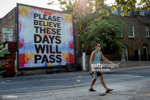 A pedestrian walks past a billboard reading Please believe these days will pass on Broadway Market in east London on April 24 2020 as life continued...
