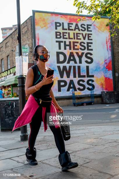 "Pedestrian walks past a billboard reading ""Please believe these days will pass"" on Broadway Market in east London on April 24, 2020 as life continued..."