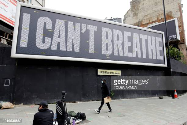 A pedestrian walks past a billboard with a slogan in support of the Black Lives Matter movement near Westminster Bridge in central London on June 12...