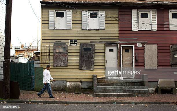 A pedestrian walks past a boarded up residence in Trenton New Jersey US on Sunday Nov 27 2011 Trenton the New Jersey capital and onetime factory hub...