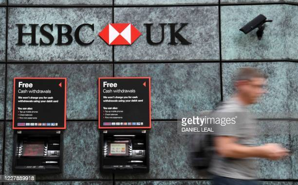Pedestrian walks past a branch of a HSBC bank in central London on August 3, 2020. - HSBC on Monday revealed a 69-percent slump in net profits,...