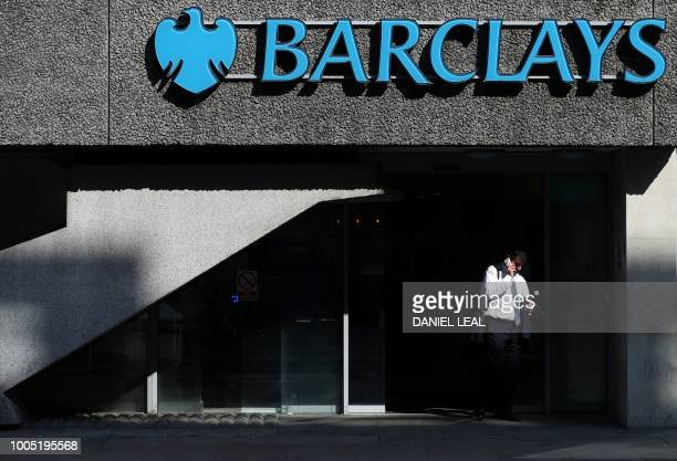 A pedestrian walks past a branch of Barclays bank in central London on July 25 2018