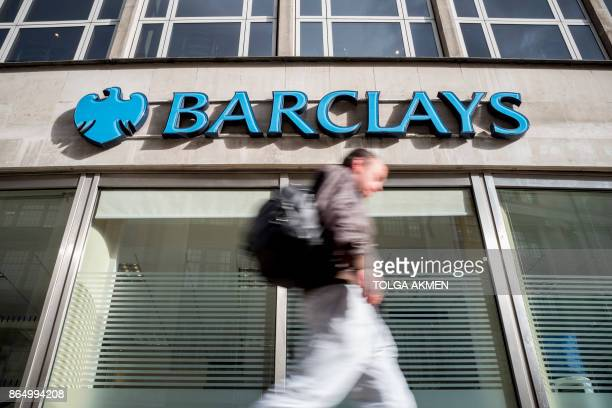 A pedestrian walks past a branch of Barclays bank in central London on October 22 2017 / AFP PHOTO / AFP PHOTO AND Tolga Akmen / Tolga Akmen