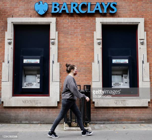 Pedestrian walks past a branch of British bank Barclays in central London on July 28, 2021. - British bank Barclays said Wednesday that first-half...