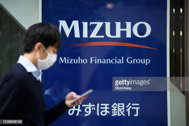 Pedestrian walks past a branch of Mizuho Bank Ltd. In Tokyo, Japan, on Monday, Nov. 9, 2020. Japanese banks expect business opportunities from...
