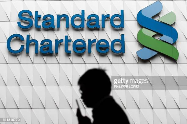 A pedestrian walks past a branch of Standard Chartered bank in Hong Kong on February 23 2016 Asiafocused bank Standard Chartered on February 23 swung...