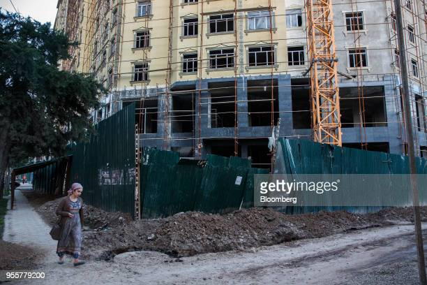 A pedestrian walks past a building under construction in Dushanbe Tajikistan on Saturday April 21 2018 Flung into independence after the Soviet Union...