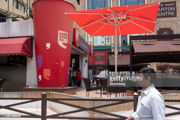 A pedestrian walks past a Cafe Coffee Day coffee shop operated by Coffee Day Enterprises ltd in Bengaluru India on Wednesday July 31 2019 VG...