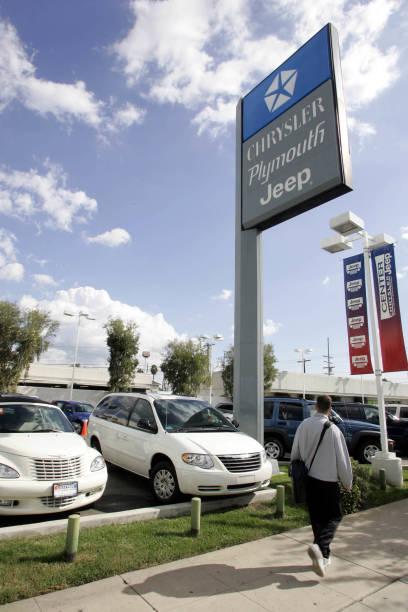 A Pedestrian Walks Past A Chrysler Dealership In Van Nuys C - Chrysler dealership