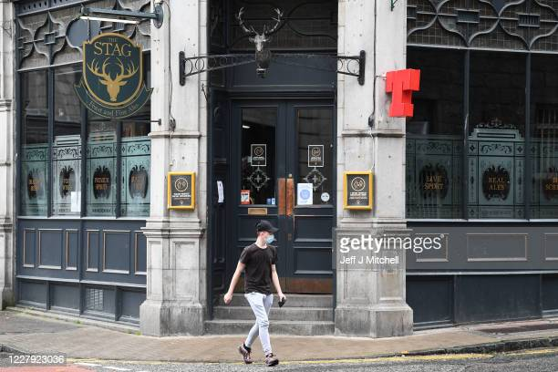 Pedestrian walks past a closed pub on August 5, 2020 in Aberdeen, Scotland. Scotland's First Minister Nicola Sturgeon acted swiftly and put Aberdeen...