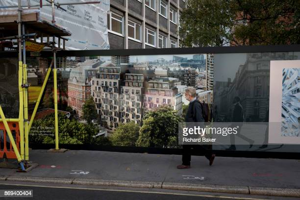 A pedestrian walks past a construction hoarding for the new luxury apartment development called The Denizen a controversial 10storey building by...