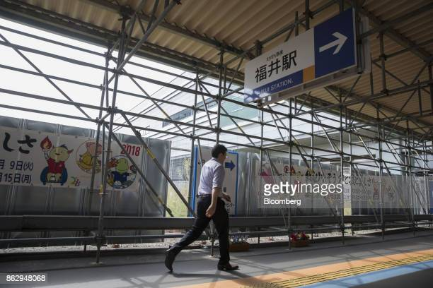 A pedestrian walks past a construction site near Fukui station in Fukui Japan on Tuesday Oct 10 2017 Fukui Prefecture has one of the lowest rates of...