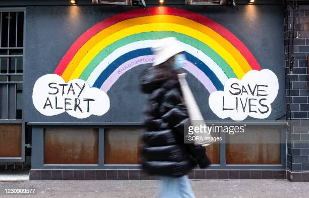 Pedestrian walks past a COVID-19 sign encouraging people to stay alert and save lives. Department of Health and Social Care recorded a total of 3 176...