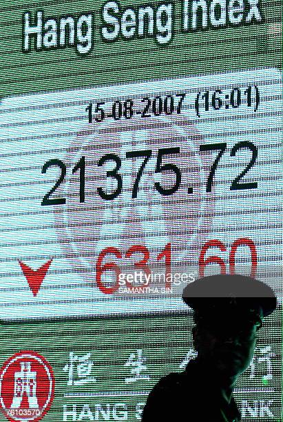 A pedestrian walks past a digital screen showing the decline in Hong Kong's Heng Seng Index 15 August 2007 Hong Kong share prices closed sharply...