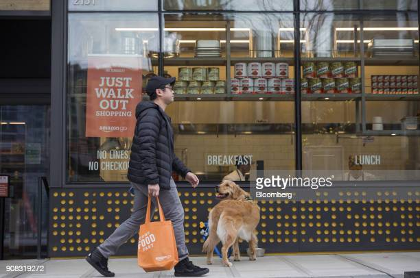 A pedestrian walks past a dog outside the Amazon Go store in Seattle Washington US on Wednesday Jan 17 2018 After more than a year of testing with an...