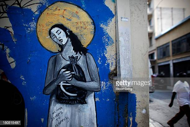 A pedestrian walks past a eurocrisis graffiti mural painted on a wall in Athens Greece on Friday Aug 17 2012 Greece's troika of international...