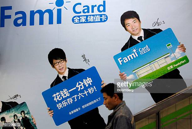 A pedestrian walks past a FamilyMart Co advertisement in Shanghai China on Sunday Jan 15 2012 FamilyMart Co Japan's largest convenience store...