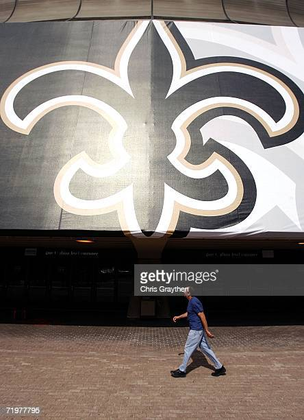 A pedestrian walks past a giant FleurdeLis outside the Louisiana Superdome as it prepares to reopen on September 23 2006 in New Orleans Louisiana The...