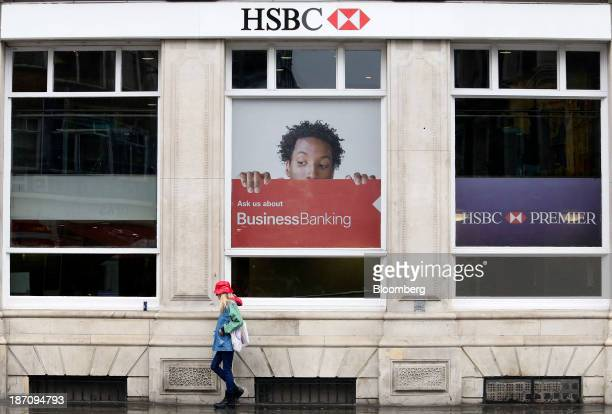 Pedestrian walks past a giant poster advertising business banking services in the window of a HSBC Holdings Plc bank branch in London, U.K., on...