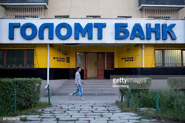 A pedestrian walks past a Golomnt Bank branch and a Western Union branch in Ulaanbaatar Mongolia on Tuesday June 24 2014 Mongolia growth has been...
