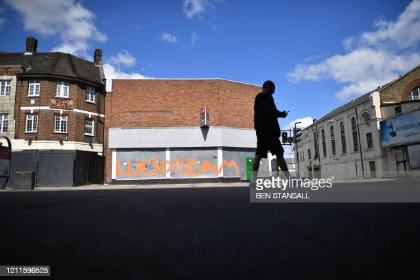 Pedestrian walks past a graffiti that reads 'Lucidream' on the shutters of a closed shop in the London borough of Newham, east London, on May 2 as...