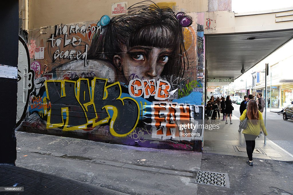 A pedestrian walks past a graffiti-covered laneway wall on the facade of a David Jones Ltd. department store in central Melbourne, Australia, on Sunday, June 2, 2013. The Australian Bureau of Statistics is scheduled to release first-quarter gross domestic product data on June 5. Photographer: Carla Gottgens/Bloomberg via Getty Images