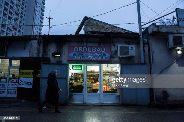 A pedestrian walks past a grocery store in Baku Azerbaijan on Saturday March 17 2018 Azerbaijan's economy barely returned to growth last year...