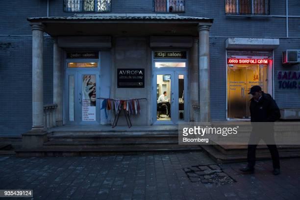 A pedestrian walks past a hairdresser's salon in Baku Azerbaijan on Saturday March 17 2018 Azerbaijan's economy barely returned to growth last year...